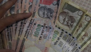 "An Indian resident holds 500 and 1000 INR notes at her home in New Delhi on November 8, 2016.  Indian Prime Minister Narendra Modi announced late November 8 that 500 and 1,000 ($15) rupee notes will be withdrawn from financial circulation from midnight, in a bid to tackle corruption. ""To break the grip of corruption and black money, we have decided that the 500 and 1,000 rupee currency notes presently in use will no longer be legal tender from midnight ie 8 November, 2016,"" Modi said in a special televised address to the nation. / AFP / PRAKASH SINGH        (Photo credit should read PRAKASH SINGH/AFP/Getty Images)"